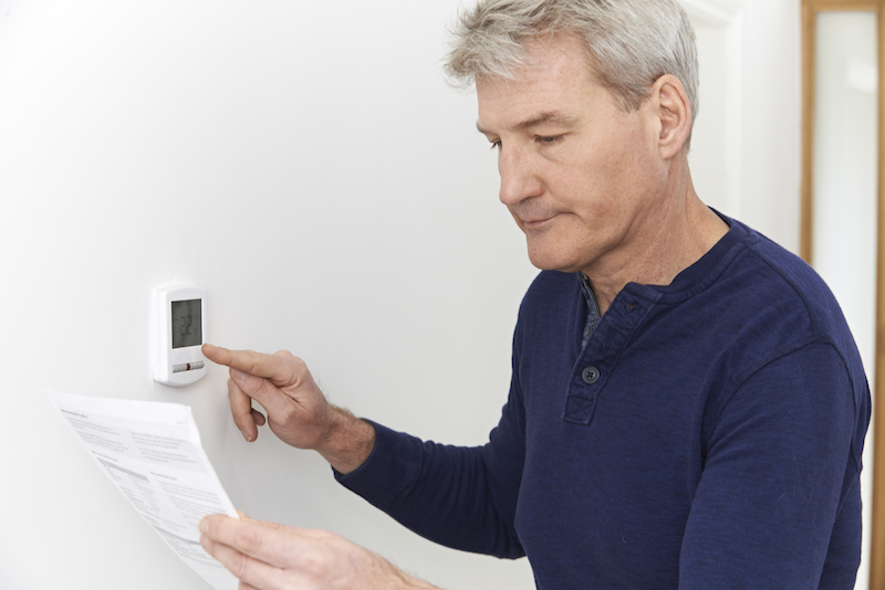 man looking at paper adjusting thermostat